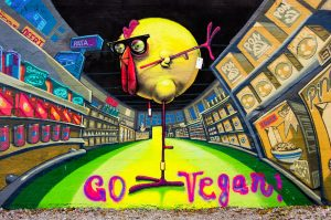 Go Vegan' graffiti on the banks of the River Limmat in Zurich, Switzerland, showing a stylised one-legged chicken in a grocery store.