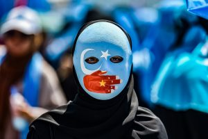 TOPSHOT - A demonstrator wearing a mask painted with the colours of the flag of East Turkestan and a hand bearing the colours of the Chinese flag attends a protest of supporters of the mostly Muslim Uighur minority and Turkish nationalists to denounce China's treatment of ethnic Uighur Muslims during a deadly riot in July 2009 in Urumqi, in front of the Chinese consulate in Istanbul, on July 5, 2018. Nearly 200 people died during a series of violent riots that broke out on July 5, 2009 over several days in Urumqi, the capital city of the Xinjiang Uyghur Autonomous Region, in northwestern China, between Uyghurs and Han people. / AFP PHOTO / OZAN KOSE