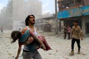 A man carries a young girl who was injured in a reported barrel-bomb attack by government forces on June 3, 2014 in Kallaseh district in the northern city of Aleppo. Some 2,000 civilians, including more than 500 children, have been killed in regime air strikes on rebel-held areas of Aleppo since January, many of them in barrel bomb attacks. AFP PHOTO / BARAA AL-HALABI