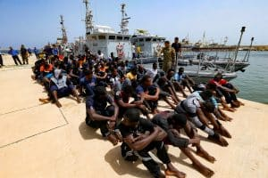 FILE PHOTO: Migrants sit at a naval base after being rescued by Libyan coastguards in Tripoli, Libya July 3, 2018. REUTERS/Ismail Zitouny/File Photo